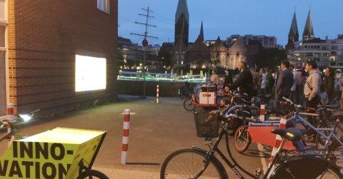 Menschenmenge schaut sich auf Fahrrädern in der Dämmerung einen Film an. Hinter ihnen die Skyline Bremen.
