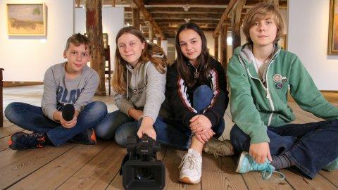 Vier Jugendliche, zwei Mädchen und zwei Jungen, sitzen auf dem Holzfußboden eines Museums. Ein Junge hält ein Mikrofon in der Hand, ein Mädchen eine Kamera. Im Hintergrund sind Bilder zu sehen.