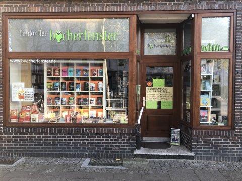 """Die Frontansicht auf das Schaufenster der Buchhandlung """"Findorffer Bücherfenster"""". Hinter der Glasscheibe stehen Bücher in Regalen."""