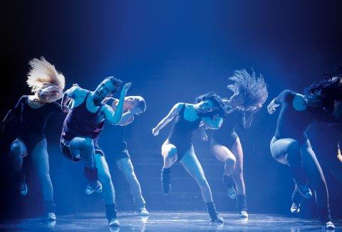 Eine Gruppe von Frauen und Männern tanzen auf einer Bühne.