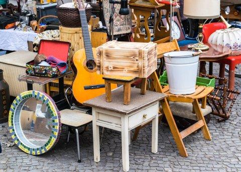 Eine Flohmarktszene von einem Stand mit kleinen Möbeln wie Nachtschränken und einer Gitarre.