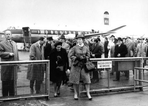 Die schwarz-weiß Aufnahme zeigt eine Personengruppe, die gerade auf dem Flughafen gelandet ist und durch ein Tor geht.