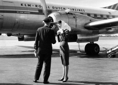 Die schwarz-weiße Aufnahme zeigt einen Piloten, der sich mit einer Stewardess auf dem Rollfeld unterhält. Im Hintergrund ist ein Flugzeug zu sehen.