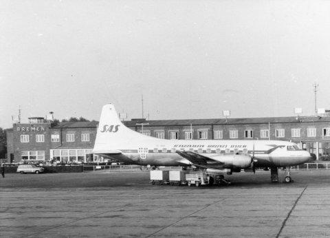 Die schwarz-weiße Aufnahme zeigt ein kleine Flugzeug auf dem Rollfeld. Im Hintergrund ist das Flughafengebäude zu sehen.