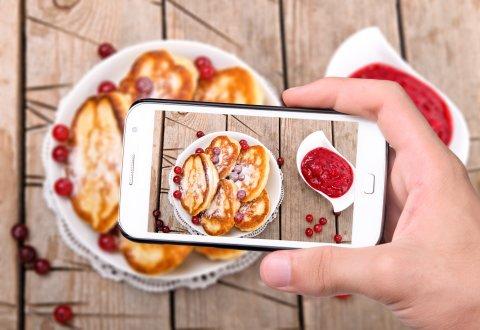 Blick durch das Kameradisplay eines Smartphones auf Pfannkuchen mit Früchten