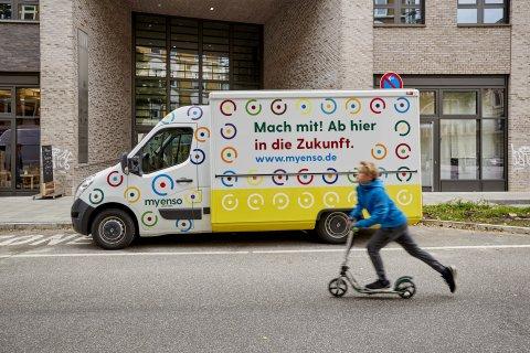 """Der """"Foodtruck"""", ein kleiner Transportwagen, von myEnso steht in einer Parklücke vor einem Gebäude."""