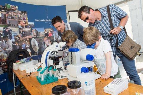 Zwei Kinder schauen durch Mikroskope, zwei Männer spähen ihnen über die Schultern.