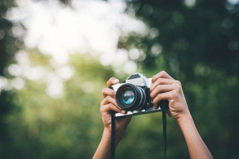Eine Kamera wird von zwei Händen in die Luft gehalten