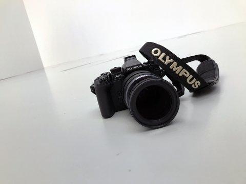 Eine Fotokamera liegt auf einem weißen Hintergrund