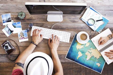 Ein Mann plant am Computer eine Reise. Neben ihm liegen eine Karte und Bilder.