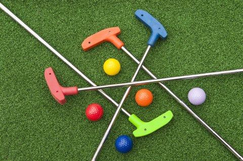Zu sehen sind vier Minigolfschläger in verschiedenen Farben und passende Bälle auf einer Grünfläche.