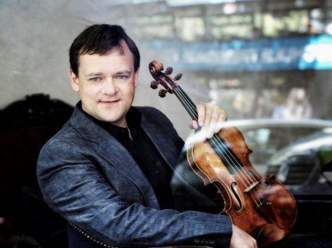 Zu sehen ist Frank-Peter Zimmermann. Er sitzt an einem Fenster und hält eine Violine in der Hand.