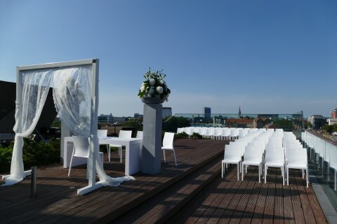 Zu sehen ist die Dachterasse des Ecos Office Center in Bremen. Die Dachterasse ist mit weißen Stühlen und Tischen bestückt. Die Kulisse deutet auf eine Hochzeit hin.