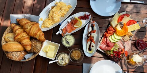 Ein reich gedeckter Frühstückstisch mit verschiedenen Aufschnitten, Käse, Lachs, Rührei und unterschiedlichen Brötchen.