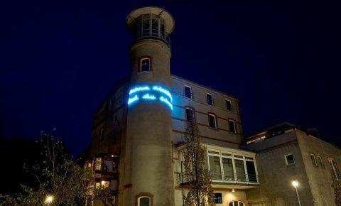 Das Gebäude der Städtischen Galerie bei Nacht, ein kleiner Turm ist mit blauer Schrift beleuchtet.