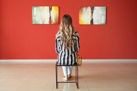 Eine Frau sitzt mit dem Rücken zur Kamera vor einer Wand, an der zwei Bilder aufgehängt sind