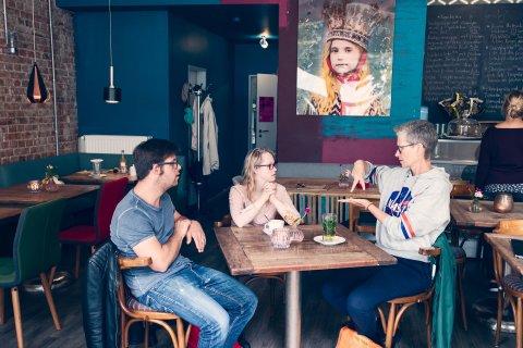 Zwei Frauen und ein Mann sitzen an einem Tisch in einem Café. Eine der Frauen spricht in Gebärdensprache.