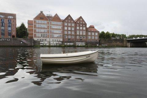 Im Vordergrund ein kleines weißes Boot mit Namen Achim auf der Weser, im Hintergrund die Weserburg