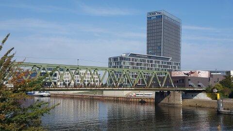 Der kleine Stadtmusikantenexpress vor den großen modernen Gebäuden der Bremer Überseestadt