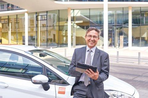 Mann im Anzug steht, ein Tablet in der Hand, grinsend vor einem Auto.