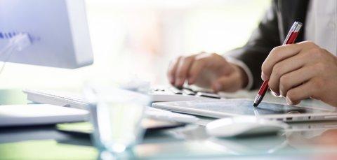 Ein Geschäftsmann kalkuliert mit Tablet und Taschenrechner.