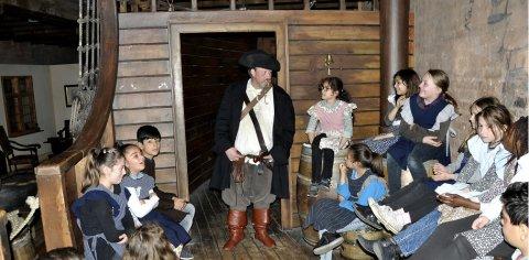 Eine Kindergruppe und ein als Pirat verkleideter Schauspieler auf einem nachgebauten Schiffteil.