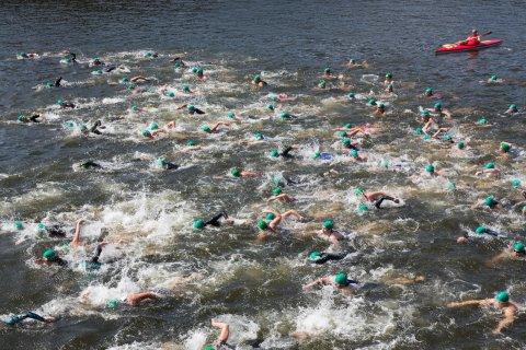 Triathlon-Teilnehmer schwimmen, während iim Hintergrund ein Kanufahrer treibt.