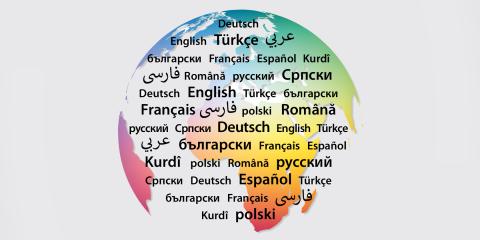 Eine Weltkugel mit verschiedenen Schriftzeichen als Symbol für Mehrsprachigkeit, darunter eine Webadresse