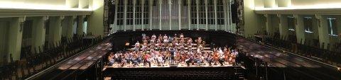 Ein Orchestra spielt in einem großen, leeren Konzertsaal. Der Saal