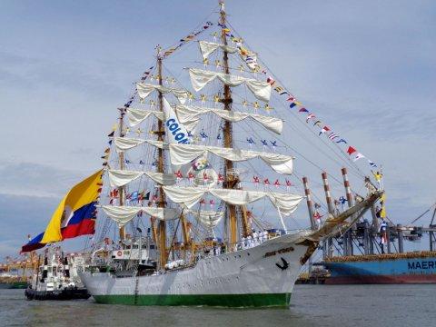Ein großes Schiff auf der Sail Bremerhaven. Am Ende des Schiffes hängt eine Kolumbienflagge. Auf den Segeln stehen Personen in roten, blauen und gelben Pullovern und winken.