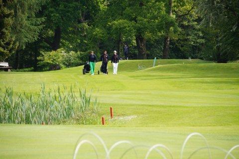 Drei Golfer ziehen ihre Taschen über die Anlage in Garlstedt