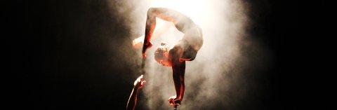 Eine Artistin macht einen Handstand auf einem schmaclen Podest und beugt Beine und Kopf Richtung Rücken