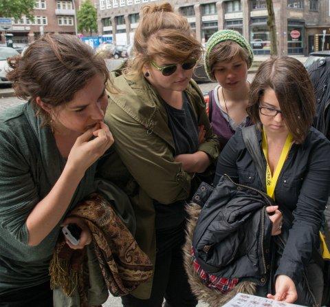 Eine Frauengruppe schaut auf einen Stadtplan. Sie haben GPS-Geräte umhängen.