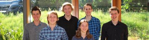 Fünf junge Männer und eine junge Frau grinsen in die Kamera