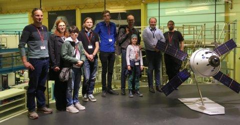 Eine Menschengruppe steht bei Airbus vor dem Reinraum hiner einem Satelliten-Modell