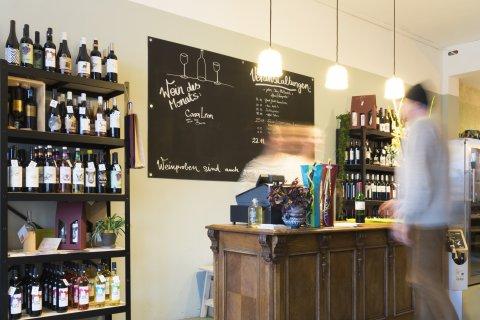Der Weinladen GluckGluck von innen. Links steht ein Regal mit verschiedenen Weinen. In der Mitte steht ein Kassentresen. Ein Mann und eine Frau stehen am Kassentresen.