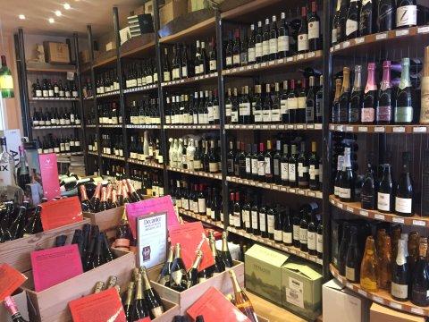 Blick auf ein Weinregal mit Rotweinen in einem Weinladen