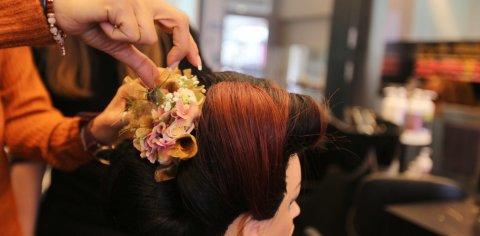 In das Haar einer Puppe werden Blumen gesteckt.
