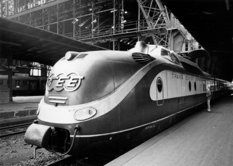 Ein großer Zug steht auf einem Gleis im Bahnhof. Ein kleiner Junge steht an einem Fenster und begutachtet ihn. Die Aufnahme ist schwarz-weiß.