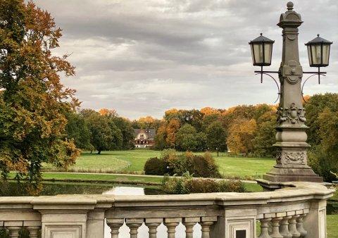 Der Bürgerpark im Herbst mit bunt gefärbten Bäumen mit Blick von einer Brücke.