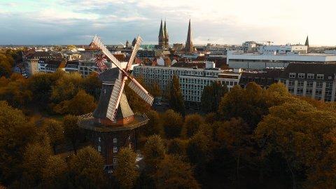 Eine Drohnenaufnahme der Mühle in Bremen umgeben von bunten Bäumen.