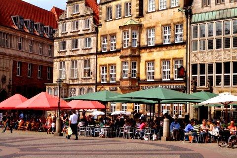 Geschäftiges Treiben bei Sonnenschein auf der Terrasse eines Straßencafés auf dem Bremer Marktplatz.