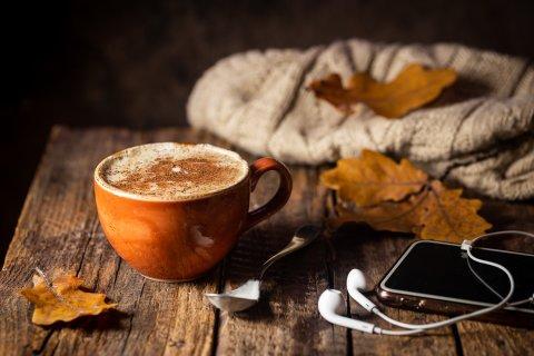 Zu sehen ist eine braune Tasse mit einem Kaffee. Daneben liegt ein Iphone mit Kopfhörern und ein bräunliches Ahornblatt. Das Bild wirkt sehr herbstlich.