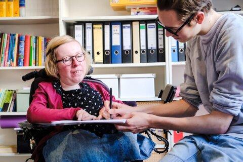 Eine Frau sitzt in einem Rollstuhl mit Rollstuhltisch. Neben ihr sitzt ein Mann und schreibt etwas auf ein Papier, das auf dem Rollstuhltisch liegt. Im Hintergrund sind Regale mit Aktenordnern und Büchern zu sehen.
