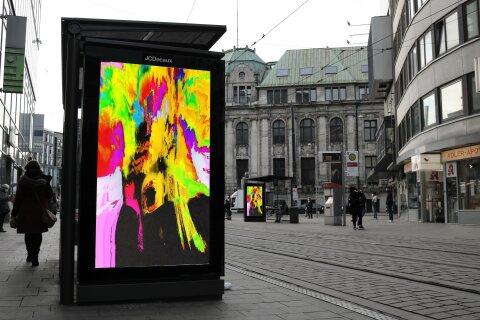 Ein buntes Kunstwerk leuchtet in der Werbeanzeige einer Haltestelle in Bremen.