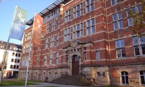 Außenansicht eines Backsteingebäudes, im Vordergrund wehen zwei Fahnen mit der Aufschrift 'Hochschule Bremen'; Quelle: WFB/bremen.online - MDR
