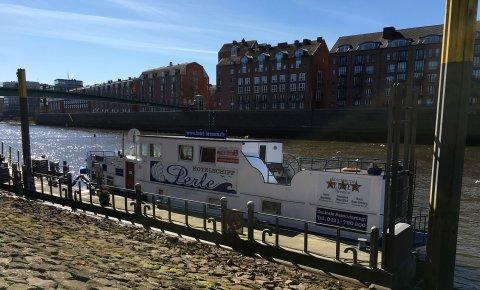 Das Hotelschiff Perle liegt an seinem Anleger an der Weser.