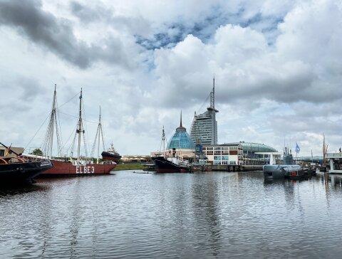 In einem Hafenbecken schwimmen mehrere Schiffe und ein altes Uboot. Im Hintergrund ist ein großes Hotel und ein Einkaufszentrum zu sehen.