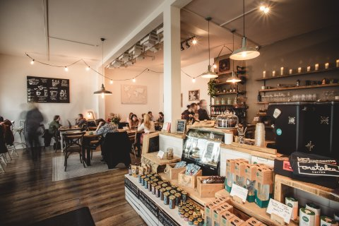 Das Café von innen. Auf Palletten sind verschiedene Kaffeesorten aufgestellt und es sitzen verschiedene Gäste im Café.