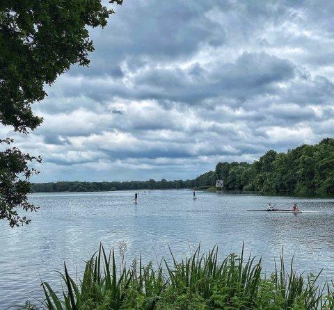 Der Unisee mit Menschen auf Stand-up-Paddle-Boards. Der Himmel ist bewölkt. An den Seiten sind grüne Bäume zu sehen.